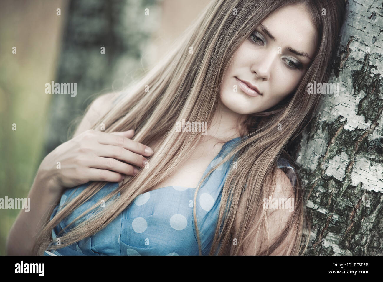 Young woman standing at the birch trunk portrait. - Stock Image