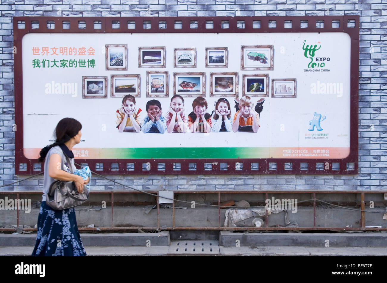 Woman passes a billboard of the coming EXPO 2010 in Shanghai. China - Stock Image