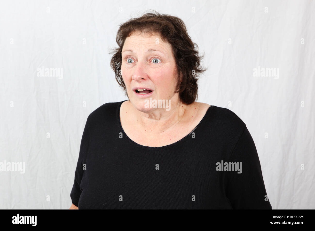 Shocked and startled middle aged woman with wide eyes looking surprised aghast and stunned - Stock Image