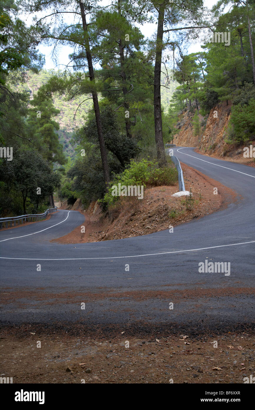twisty hairpin bend in a mountain road in the troodos mountains forest republic of cyprus - Stock Image