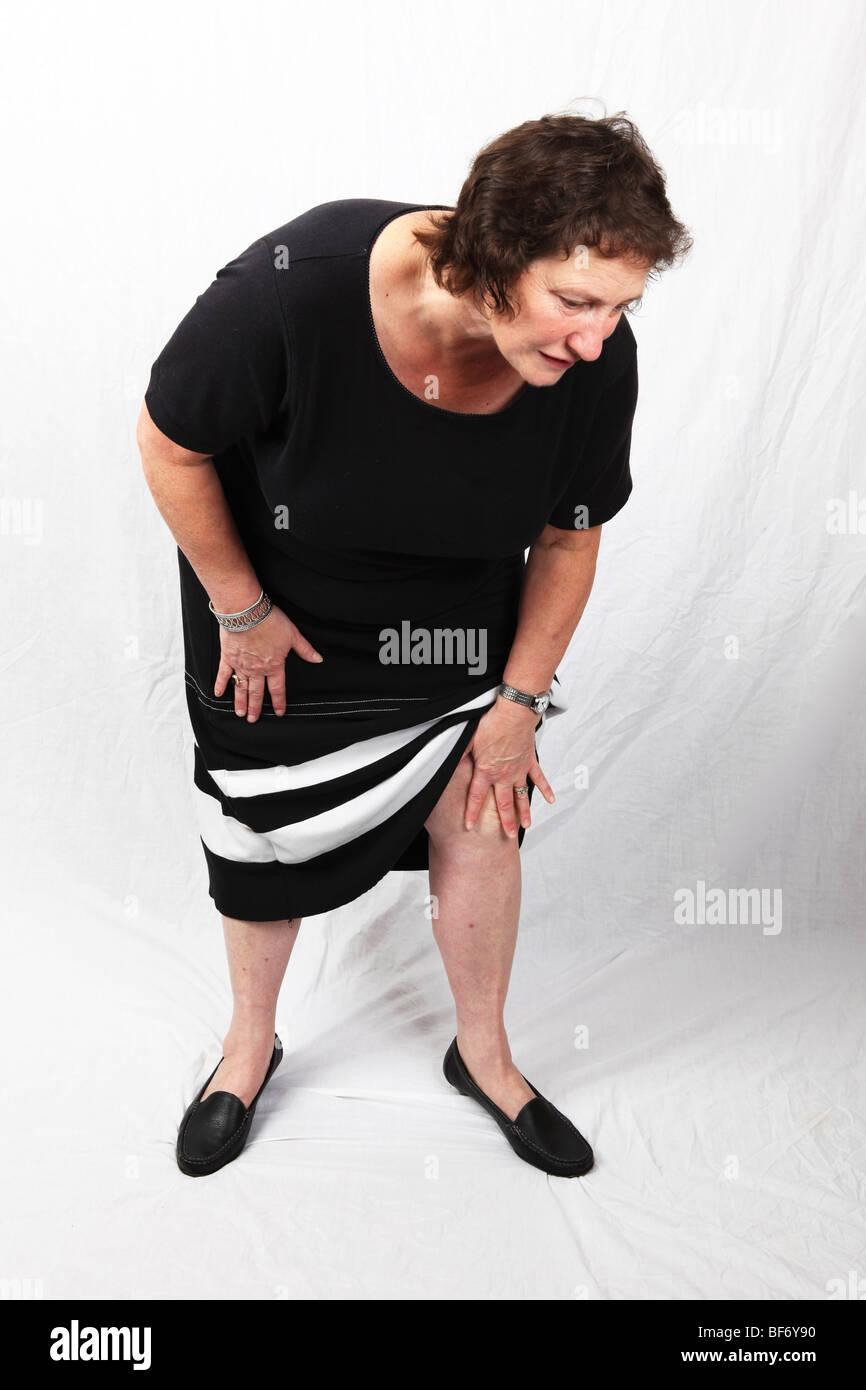 50s 60s woman holding sore knee suffering from chronic severe Osteoarthritis arthritis join pain - Stock Image