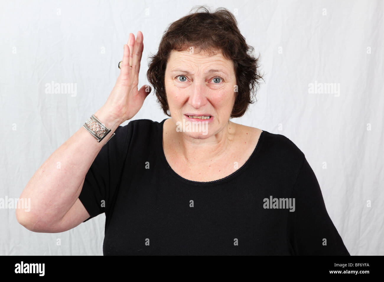 Angry 50s 60s late middle aged woman shows frustration with hand held in air looking menacing threatening violence - Stock Image