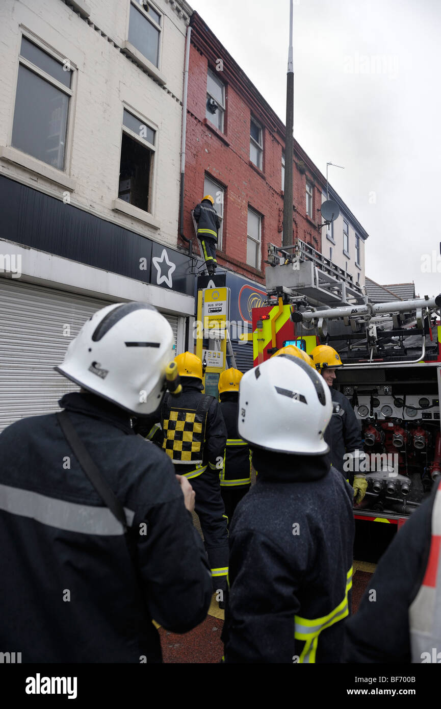 Firemen at flat fire above shop - Stock Image