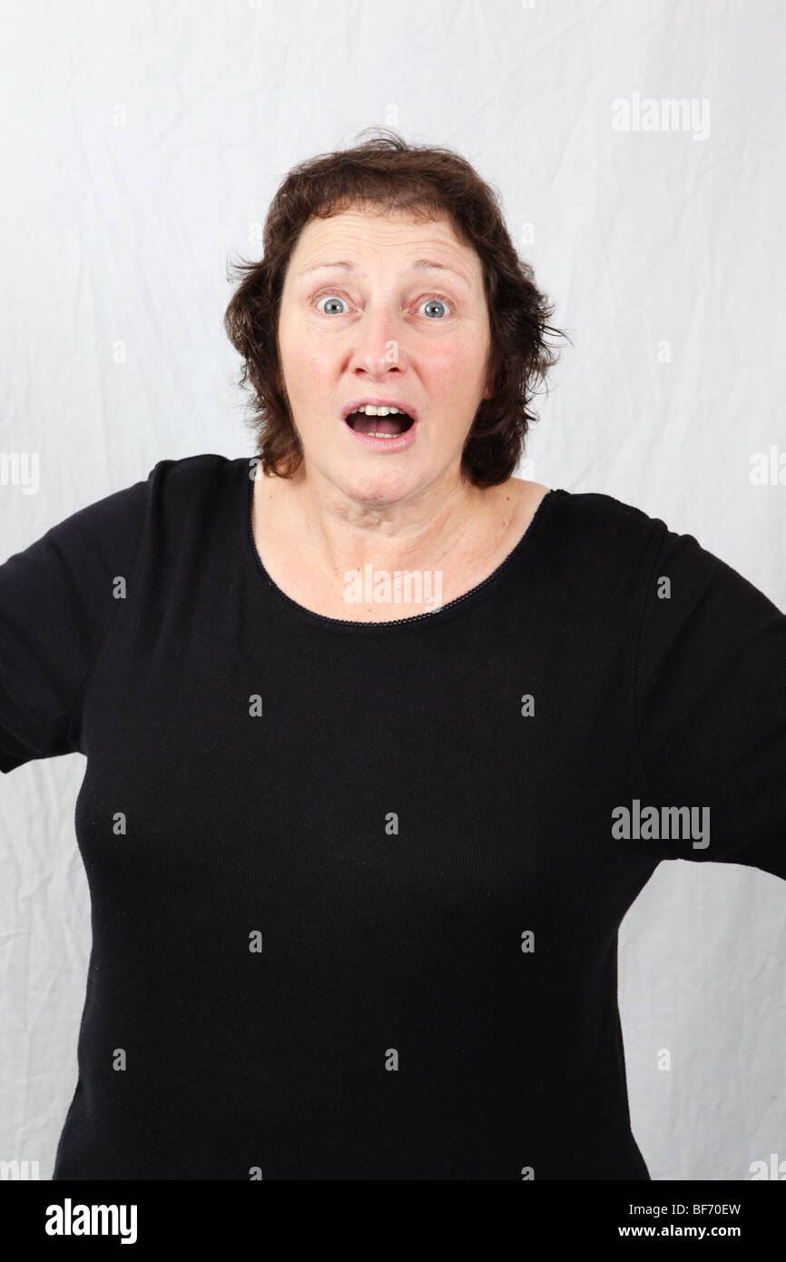 Surprised looking late middle aged woman 50s 60s year old with amazed stunned dazed overwhelmed facial expression - Stock Image