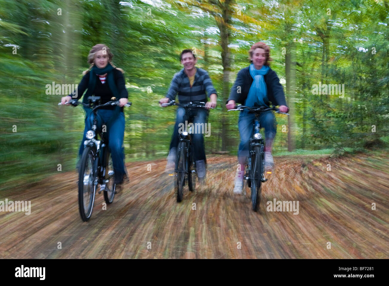 Three teenagers ride their electric bikes along a woodland track in autumn (motion blur) - Stock Image