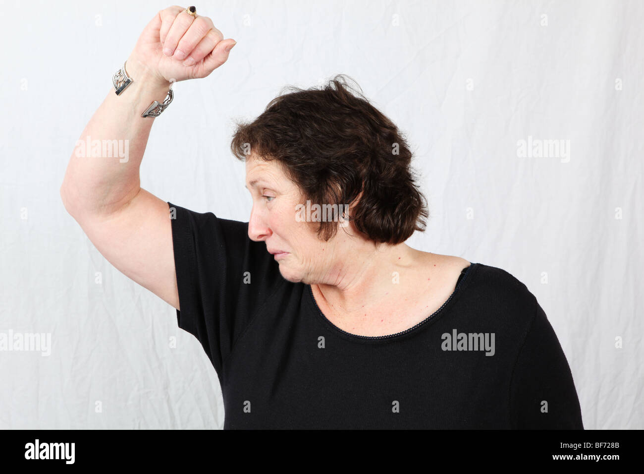 50s 60s woman smells armpit disgust smells strong under arm body odor odour BO unwashed unclean poor bad personal - Stock Image