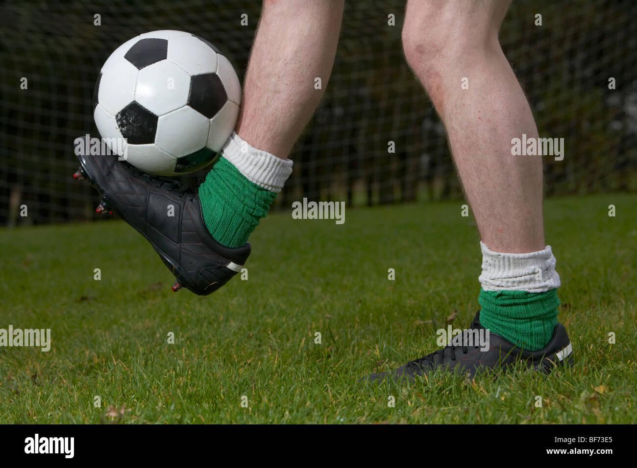 soccer football player balancing ball on one foot - Stock Image