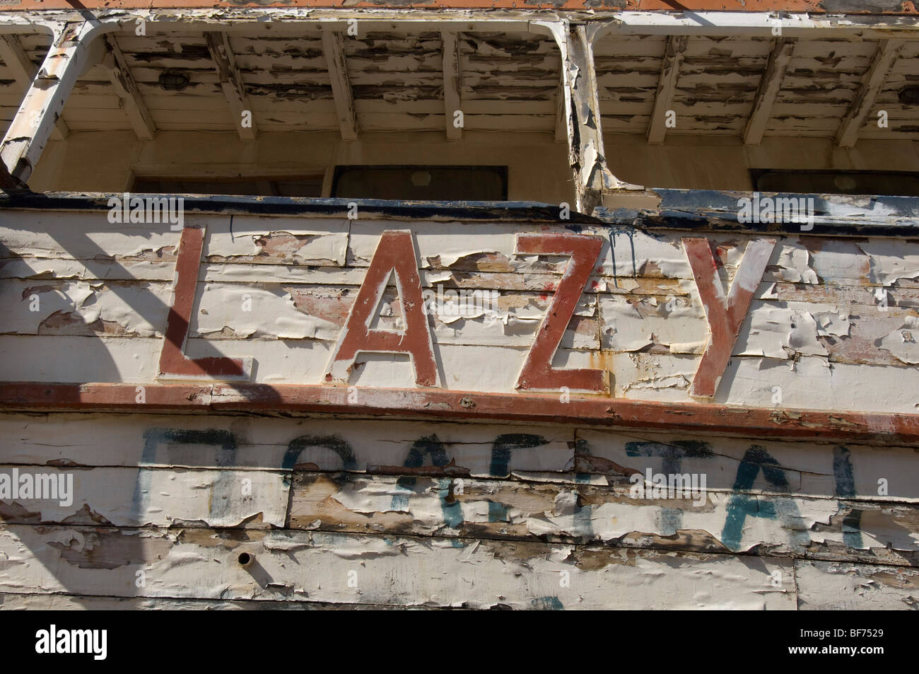 Flaking paint on an old pleasure steamer called 'Lazy Days' awaiting restoration in a boatyard in Greece. - Stock Image