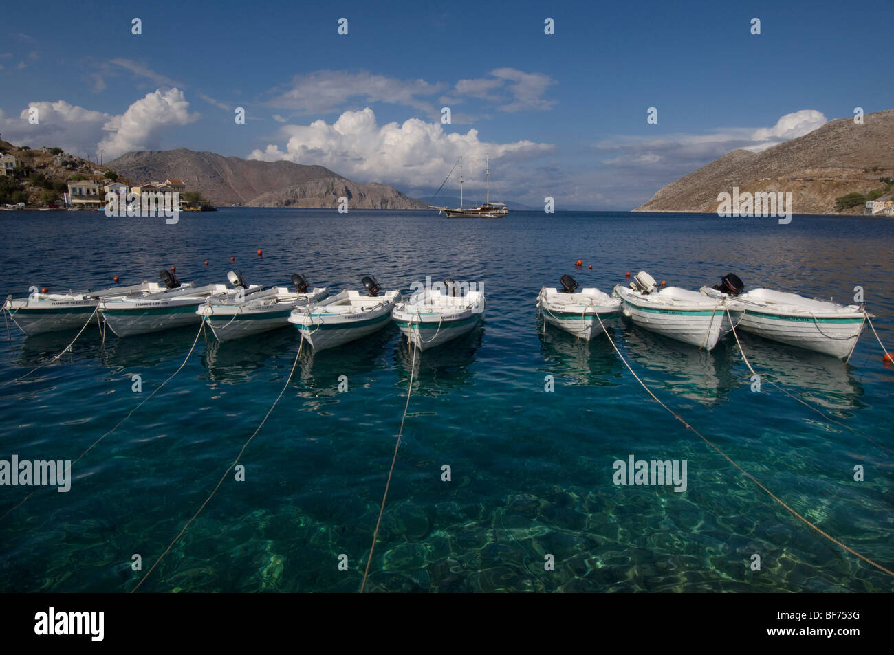A row of eight small boats moored in the harbour of Symi Town, Greece. - Stock Image