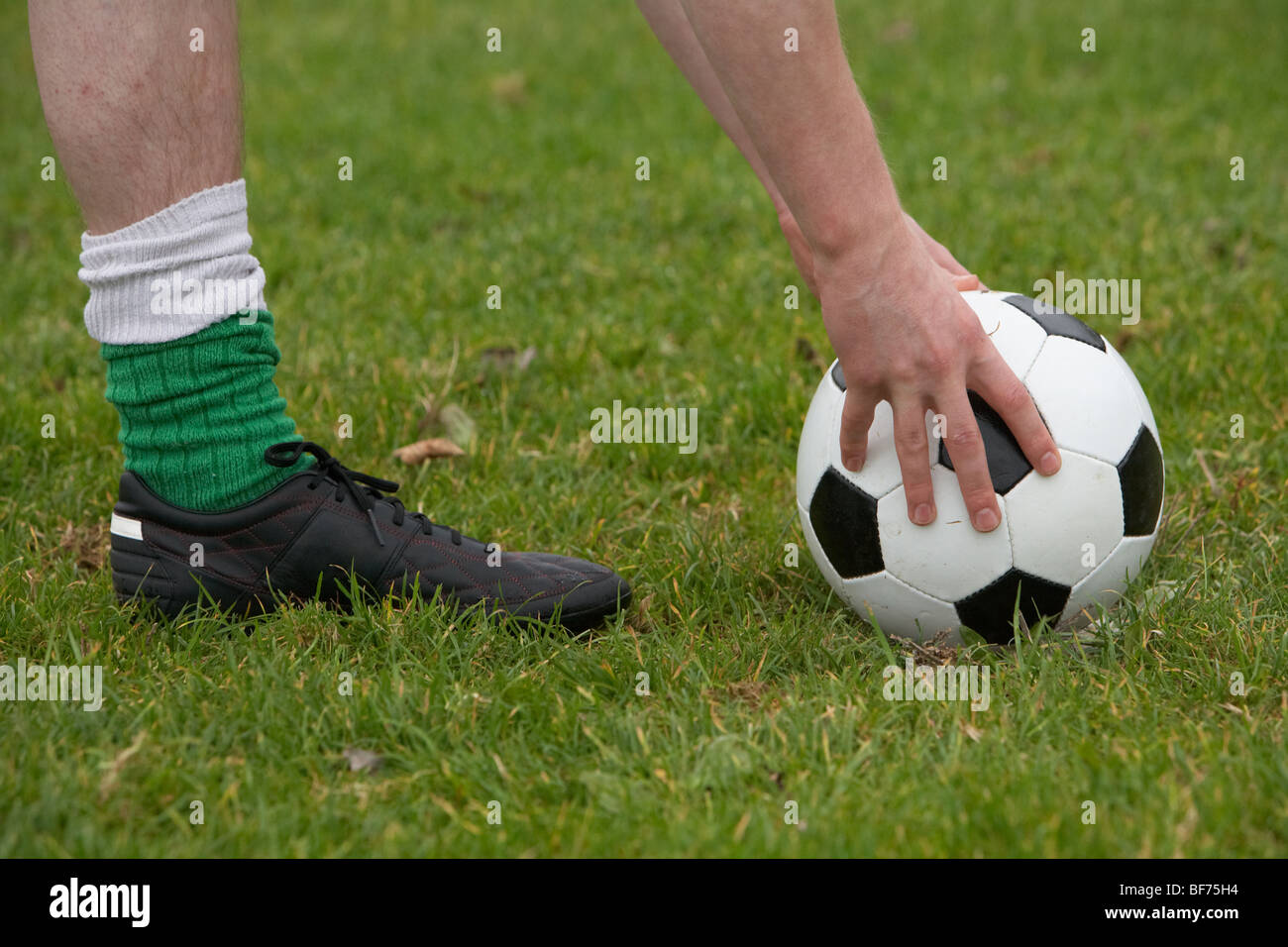 soccer football player placing the ball down for a kick - Stock Image