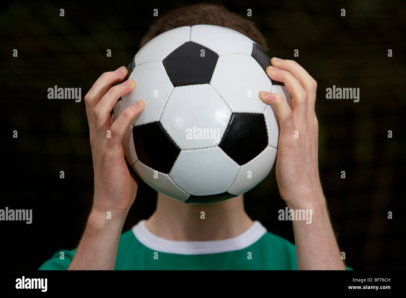 soccer football player holding ball in front of his face - Stock Image