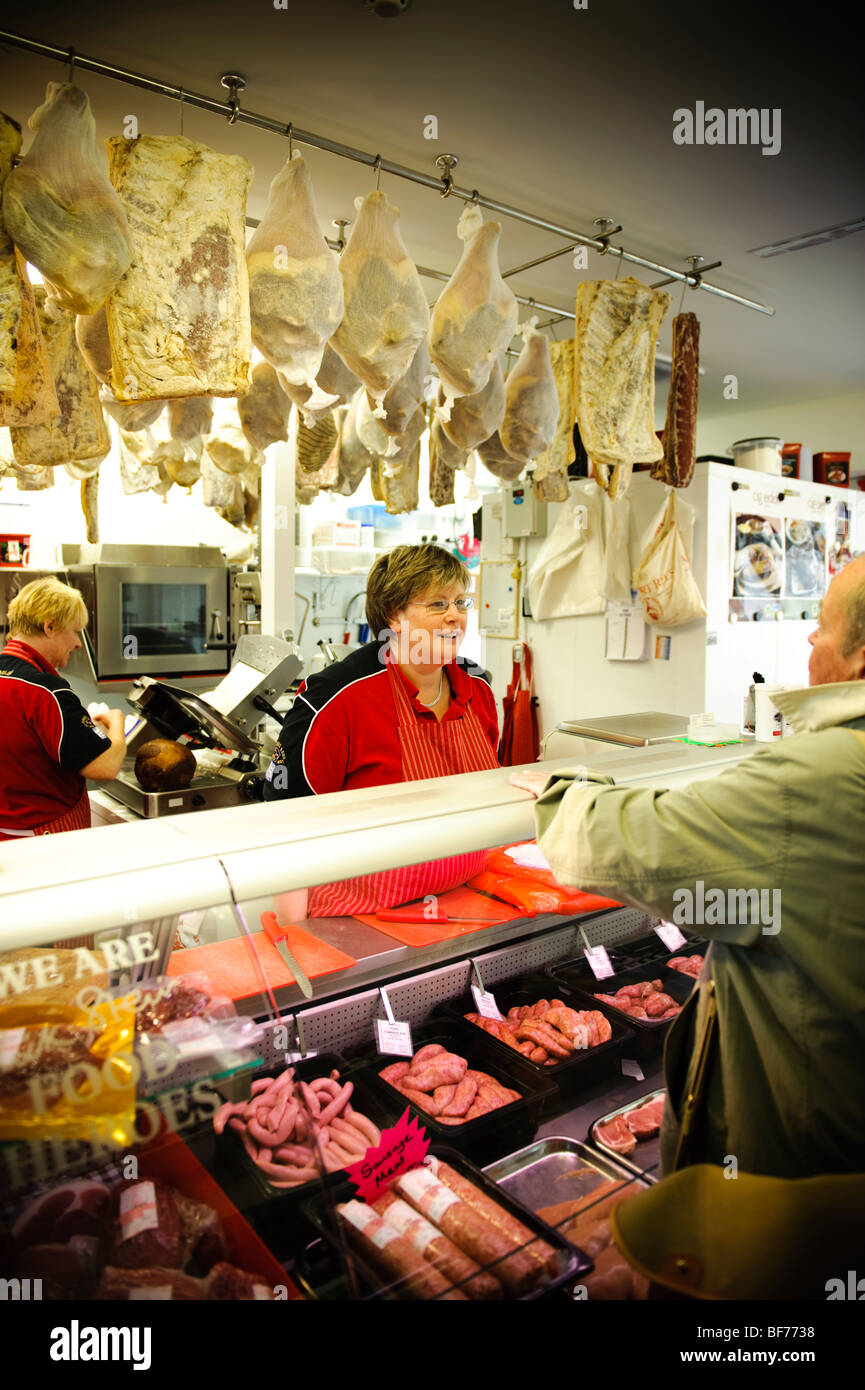 A woman working at a butchers shop stall in the new Carmarthen indoor market, Wales UK, 2009 - Stock Image