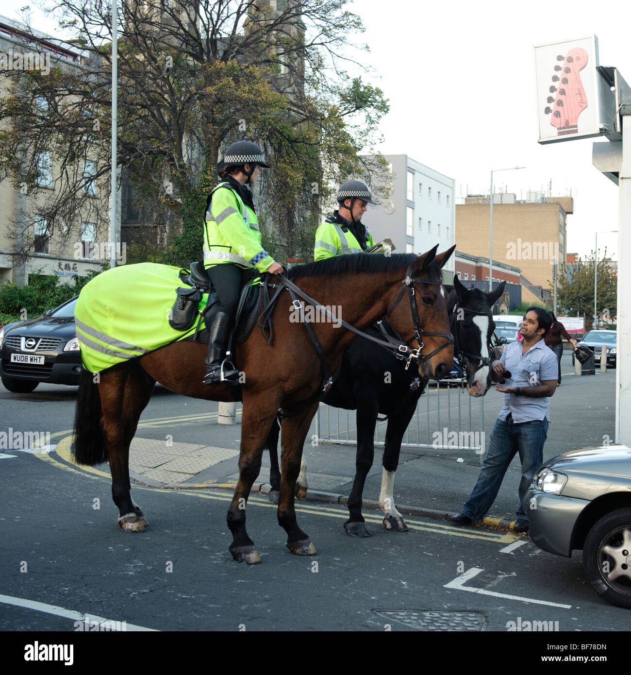 Two mounted police officers cops on horseback talking to a member of the public in Swansea city centre, Wales UK - Stock Image