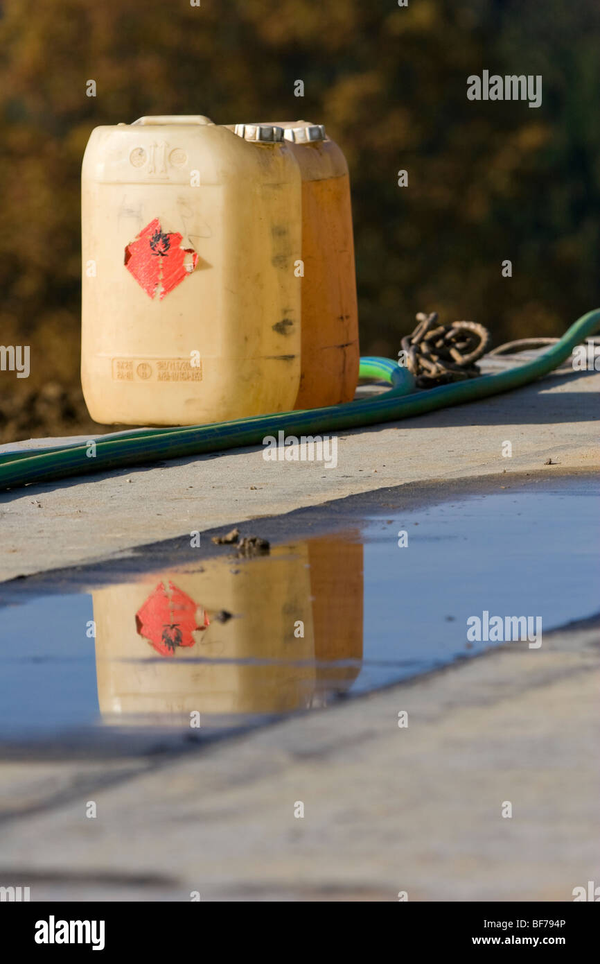 Two cans of fuel and their reflection. - Stock Image