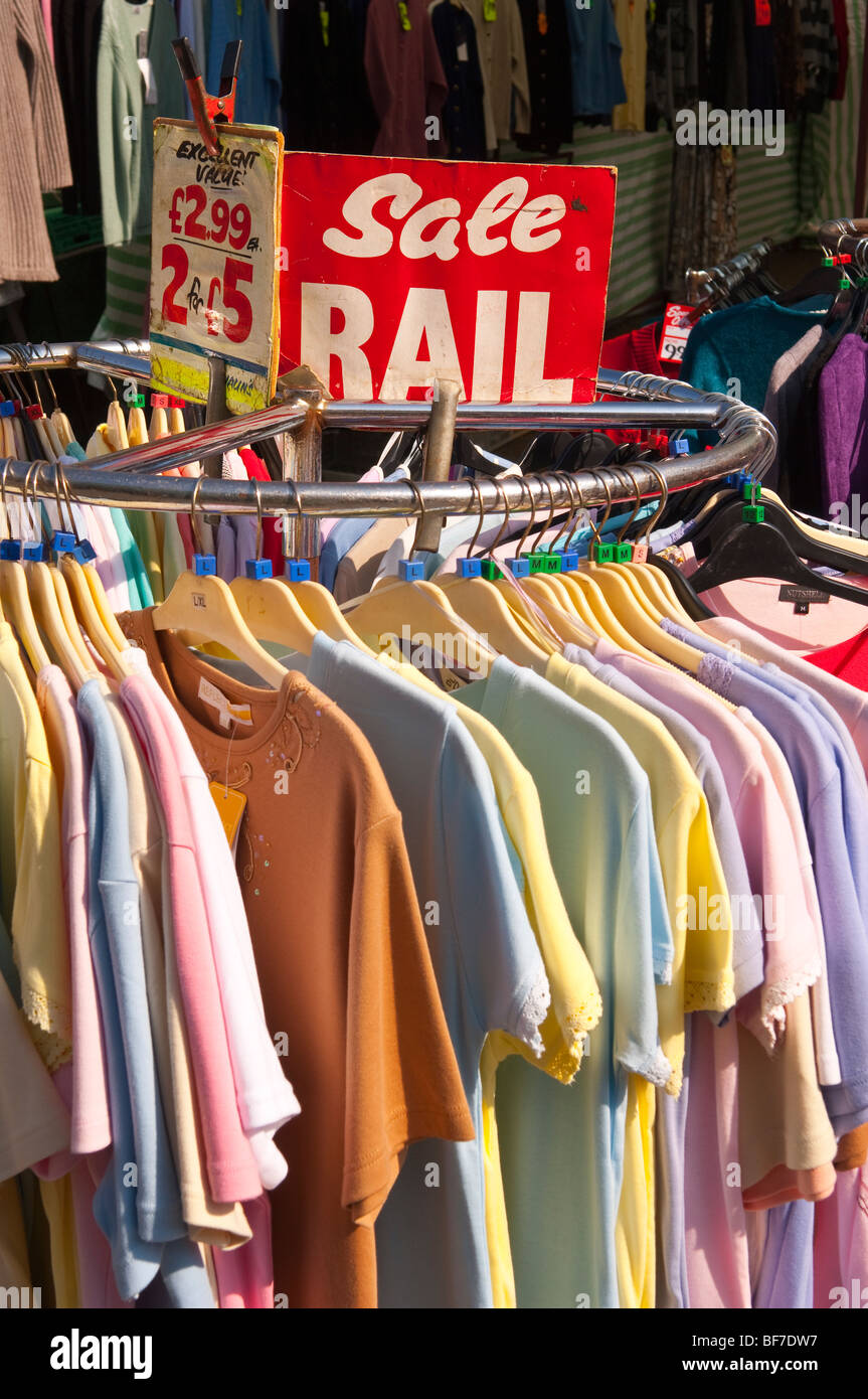 T shirts on a sale rail for sale on an outdoor market stall in Diss,Norfolk,Uk - Stock Image