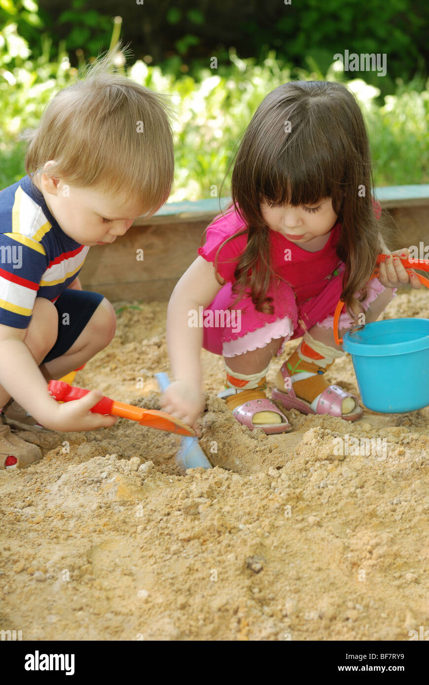 The boy and girl playing to a sandbox. Caucasian the child, park of rest - Stock Image