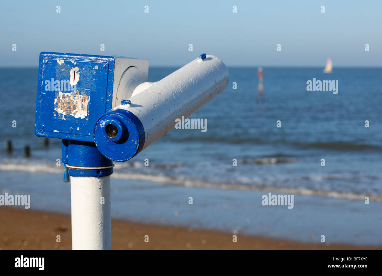 A seaside telescope looking over the sea with a distant sail visible. - Stock Image