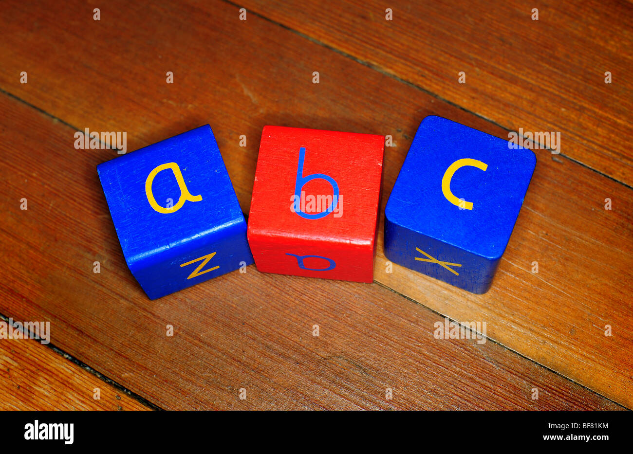 three childrens wooden blocks with a b c written on them, on a wooden floor in a nursery, to teach spelling reading - Stock Image