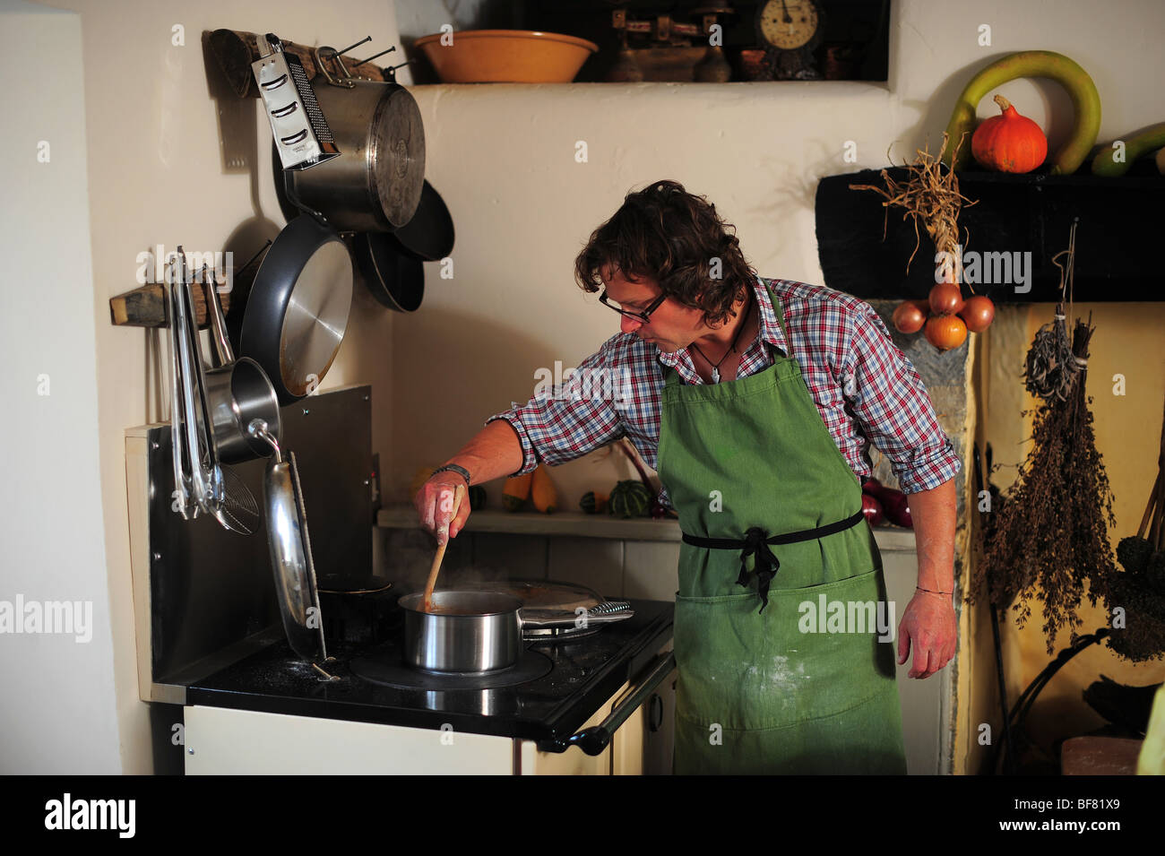hugh fearnley whittingstall pictured at River Cottage HQ preparing food at the cooker in the kitchen - Stock Image