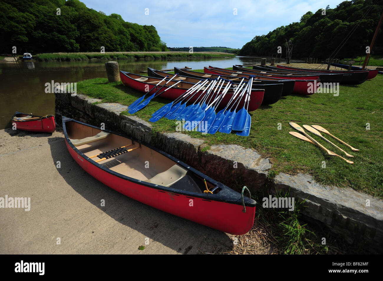 canoes and kayaks resting on the bank of the River Tamar, on the Devon and Cornwall border, UK Stock Photo