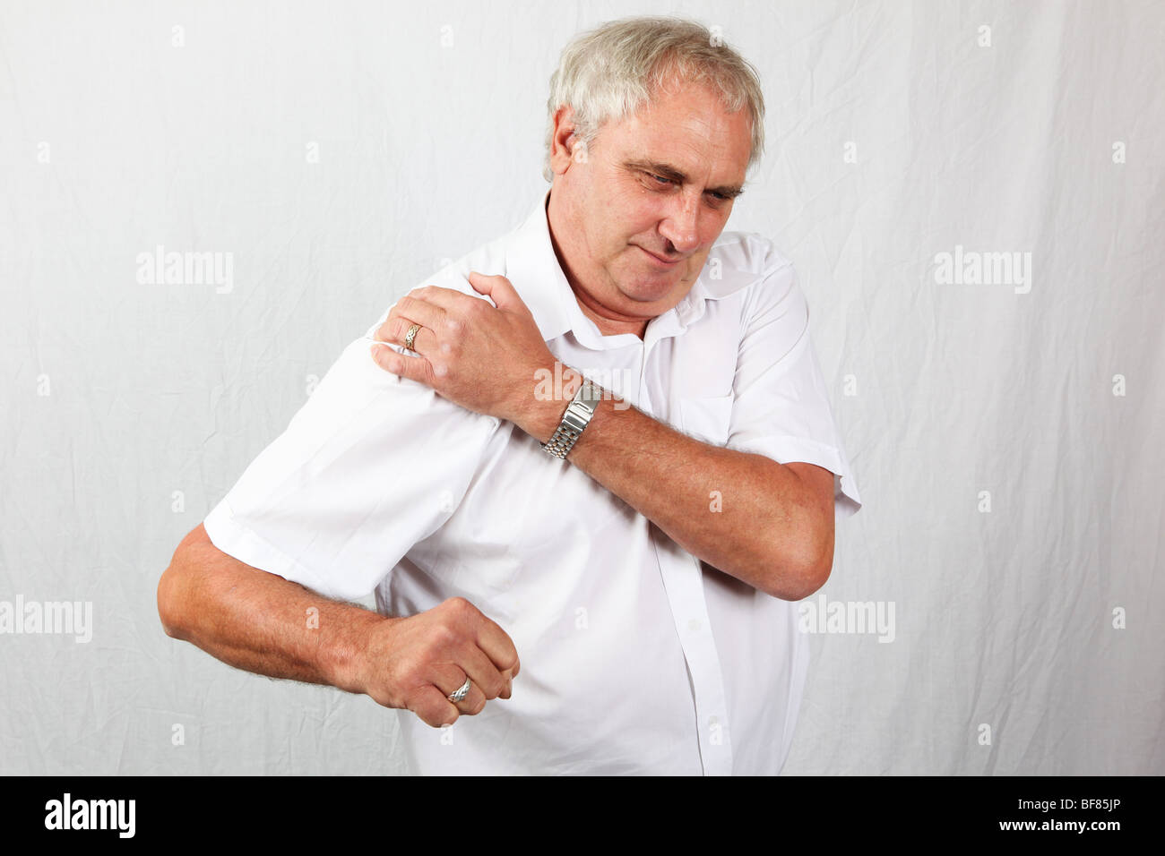 Mature 60s man suffering with osteoarthritis rheumatoid arthritis in his shoulder joint, painful inflamed stiff - Stock Image