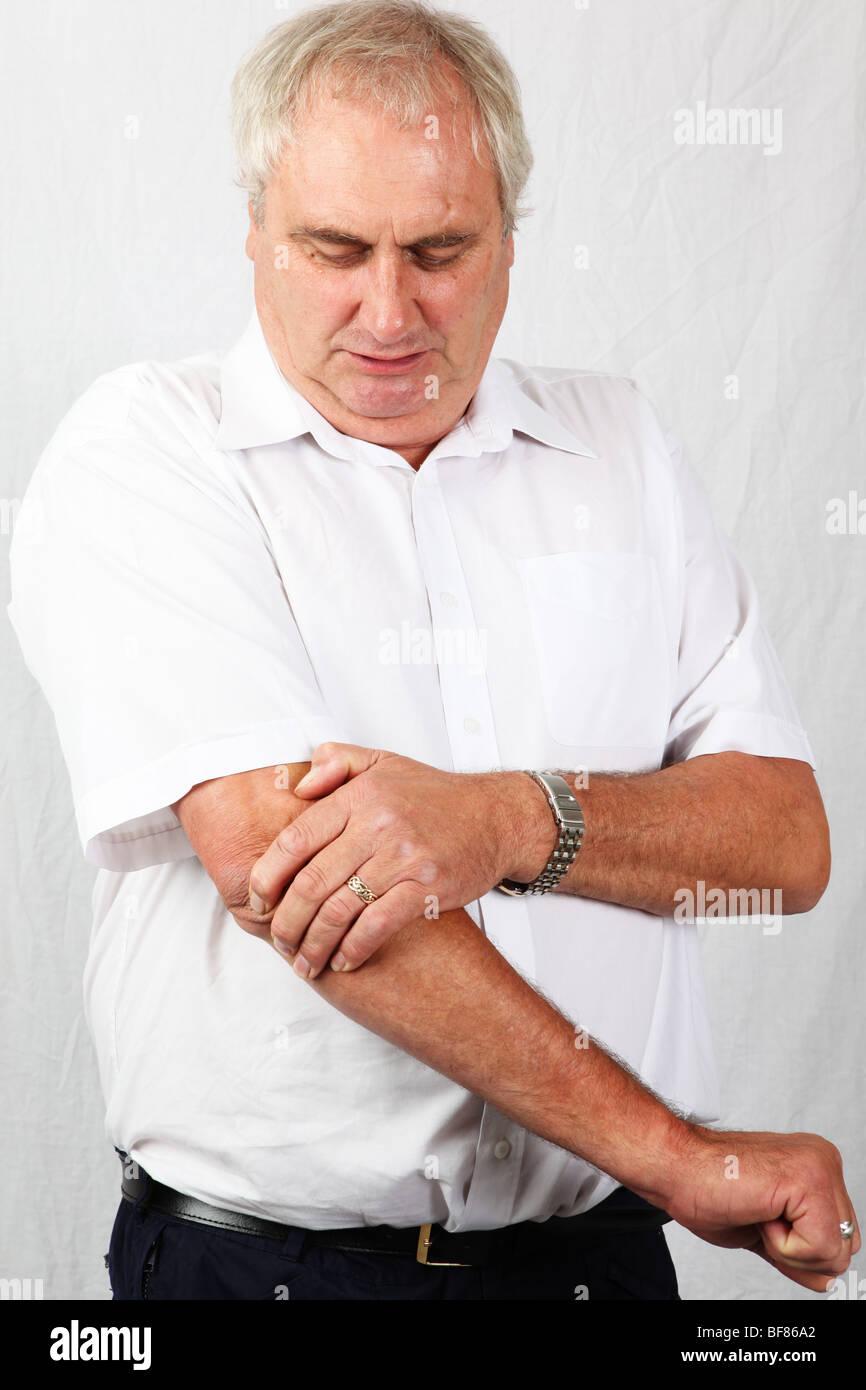 50s 60s mature grey man holding painful elbow suffering from osteoarthritis rheumatoid arthritis tennis elbow sports - Stock Image