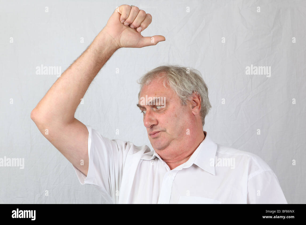 Mid 60s retired grey haired man sniffing smelling armpit checking for stale sour underarm body odour odor poor personal - Stock Image