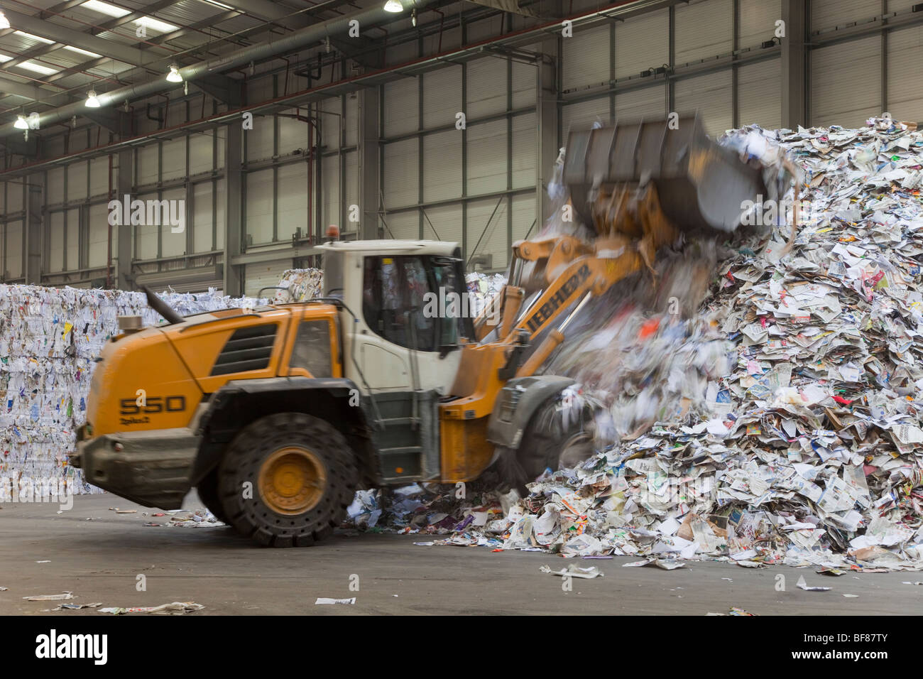 Bulldozer moving in paper  & plastic recycling factory - Stock Image