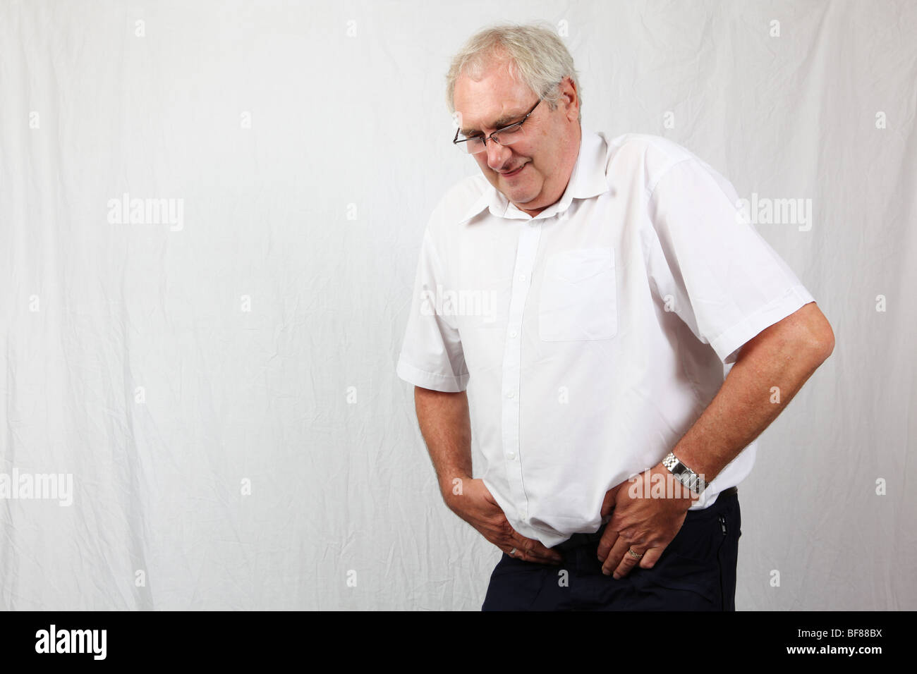 50s 60s grey haired man suffering from prostate cancer illness disease pain discomfort in groin pelvis area - Stock Image