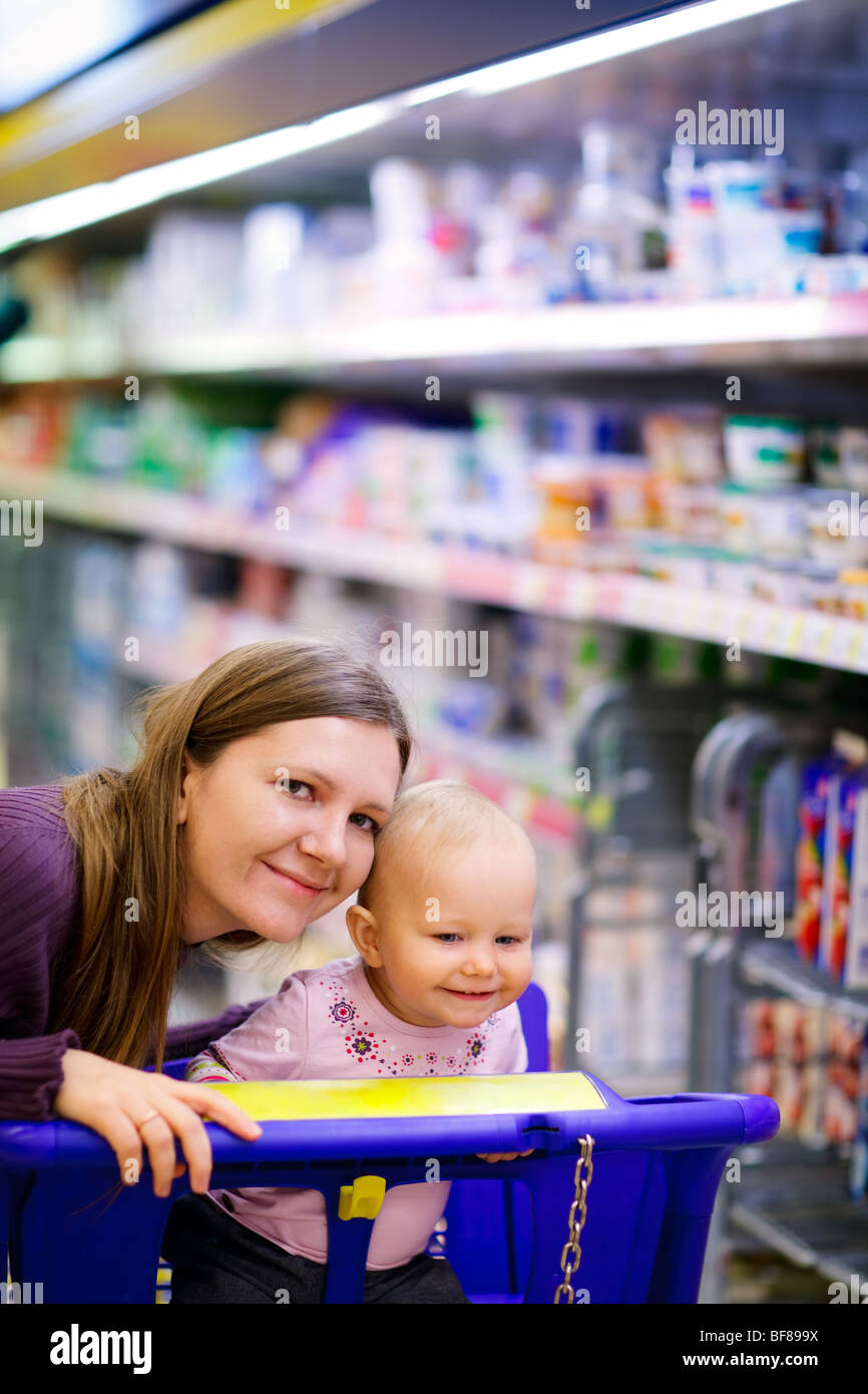 Young mother with baby daughter shopping in supermarket Stock Photo