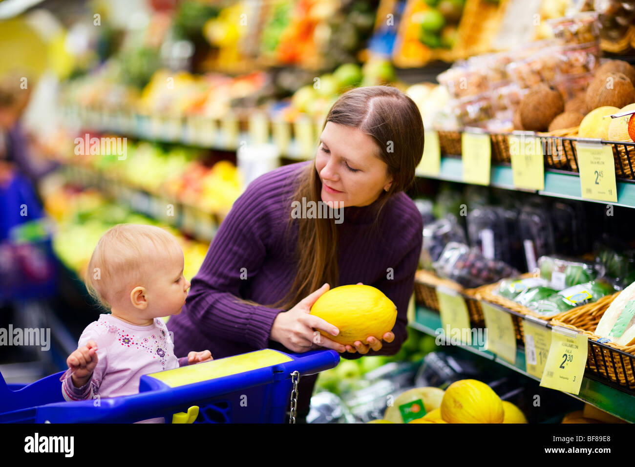 Young mother with baby daughter shopping in supermarket - Stock Image