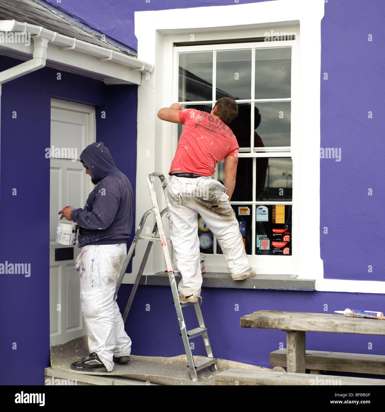 Two men gloss painting the woodwork on the exterior of a building -  door window - Stock Image