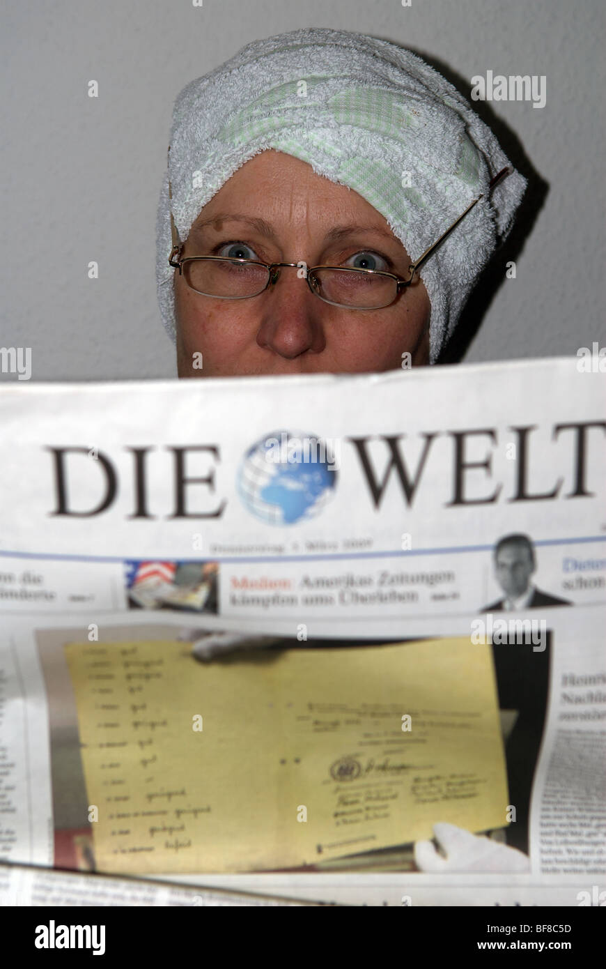 German woman reading Die Welt newspaper while drying her hair - Stock Image