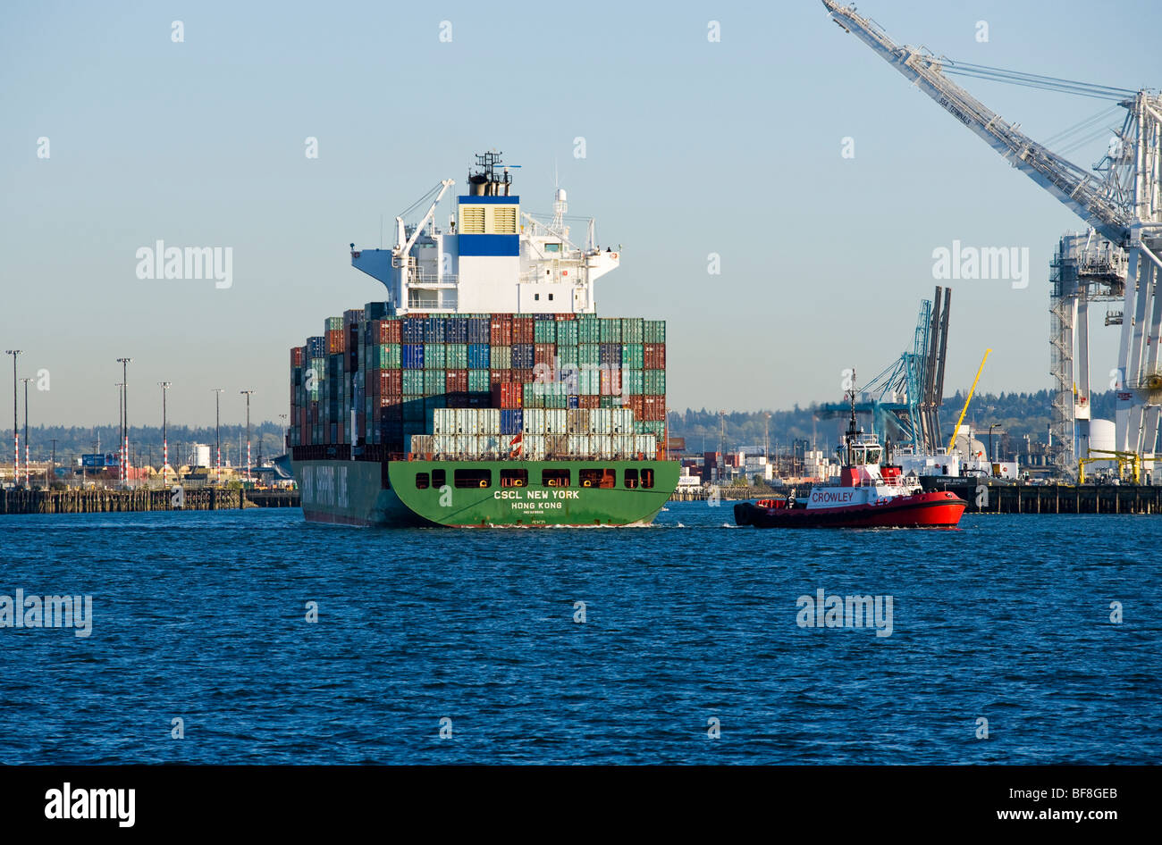 A tug boat pulls a container ship out into Elliott Bay at the Port of Seattle, Seattle, WA USA. - Stock Image