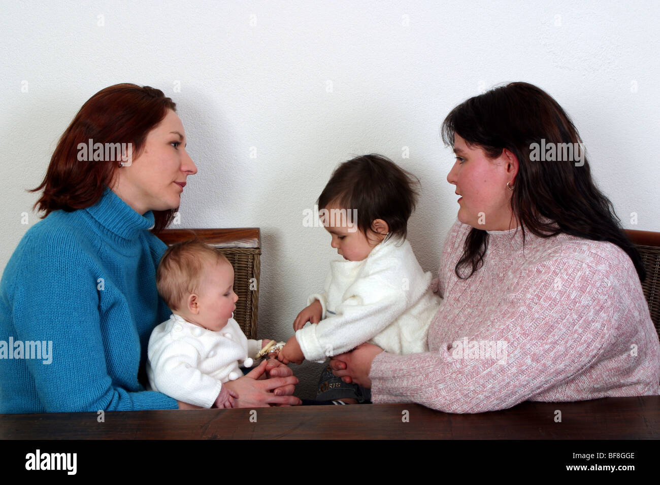Young mothers talking  sincere at home and holding babies. - Stock Image