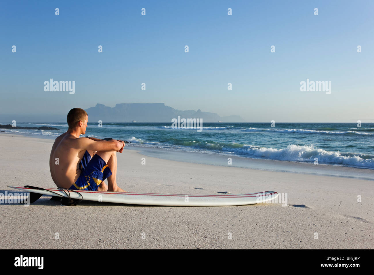 Surfer on Bloubergstrand beach with Table Mountain in background. Cape Town South Africa - Stock Image