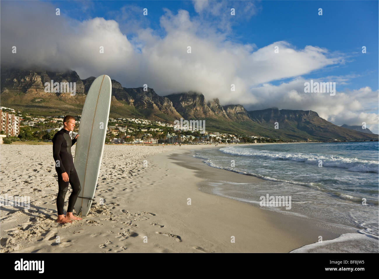 Surfer on camps bay beach with twelve apostles of Table Mountain in background. Cape Town South Africa - Stock Image