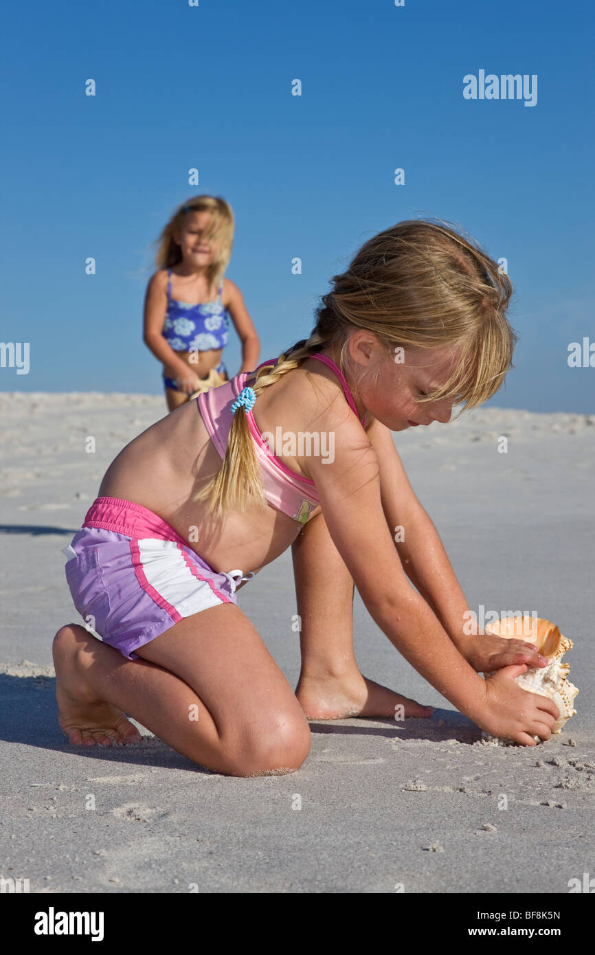 Two Sisters Wearing Swimming Costumes Playing With Shells On The
