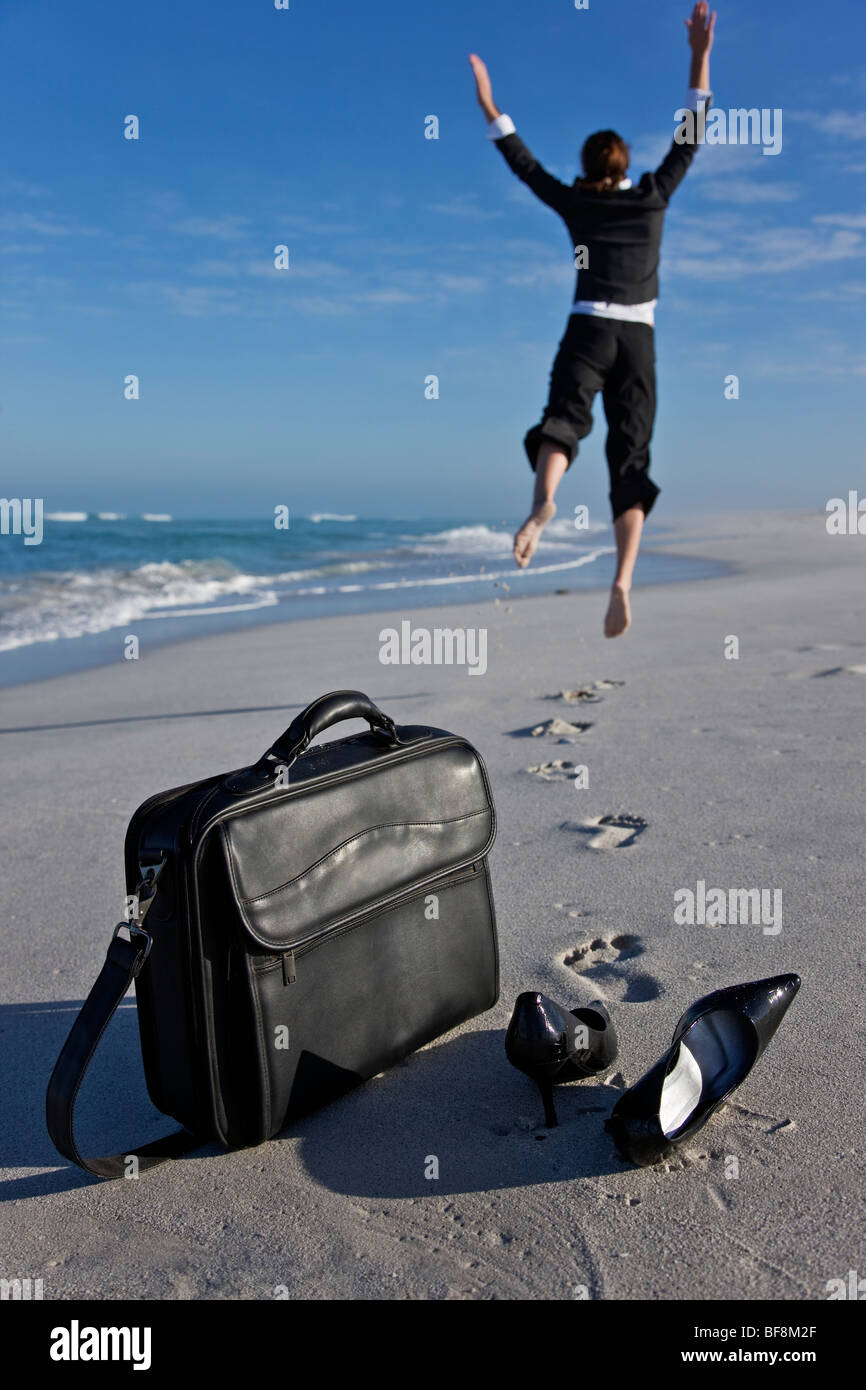 Woman in office clothes on beach jumping with joy and freedom. Laptop case and shoes in foreground. - Stock Image