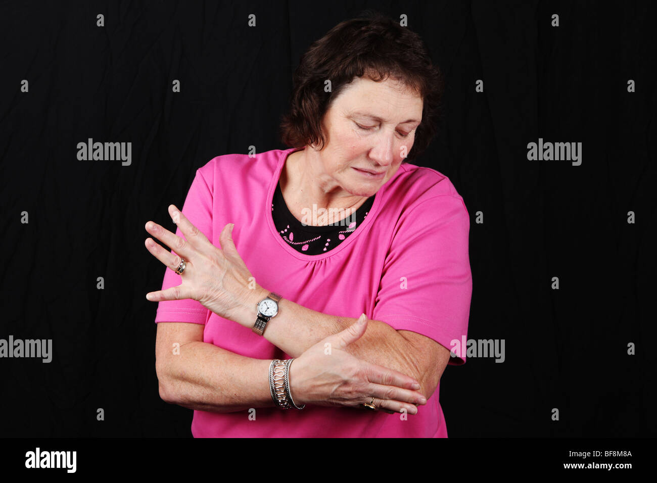 Late middle aged woman holding elbow joint suffering from severe arthritis pain tennis elbow or sports related injury - Stock Image