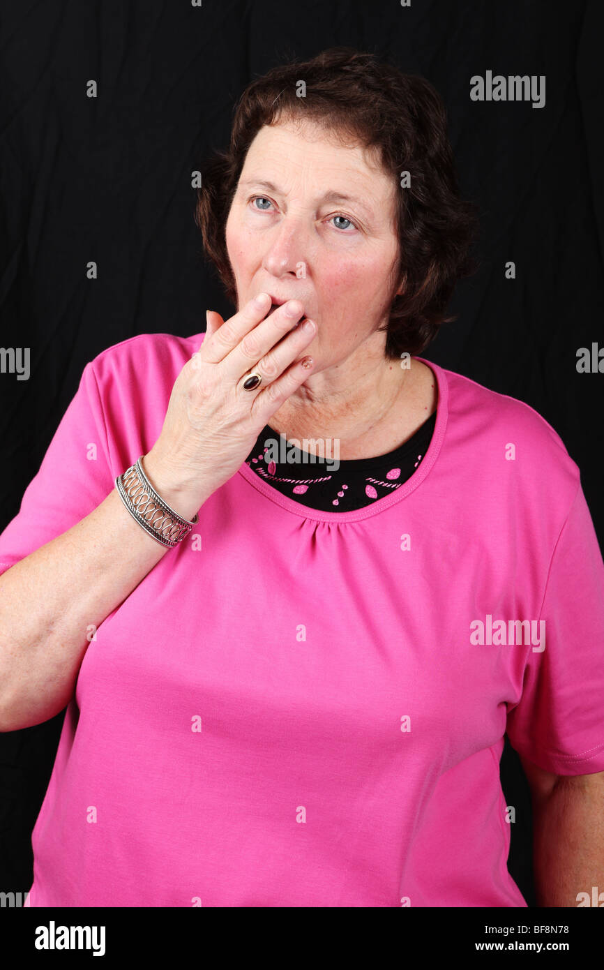 Late middle aged woman covers mouth while yawning feeling tired fatigued - Stock Image