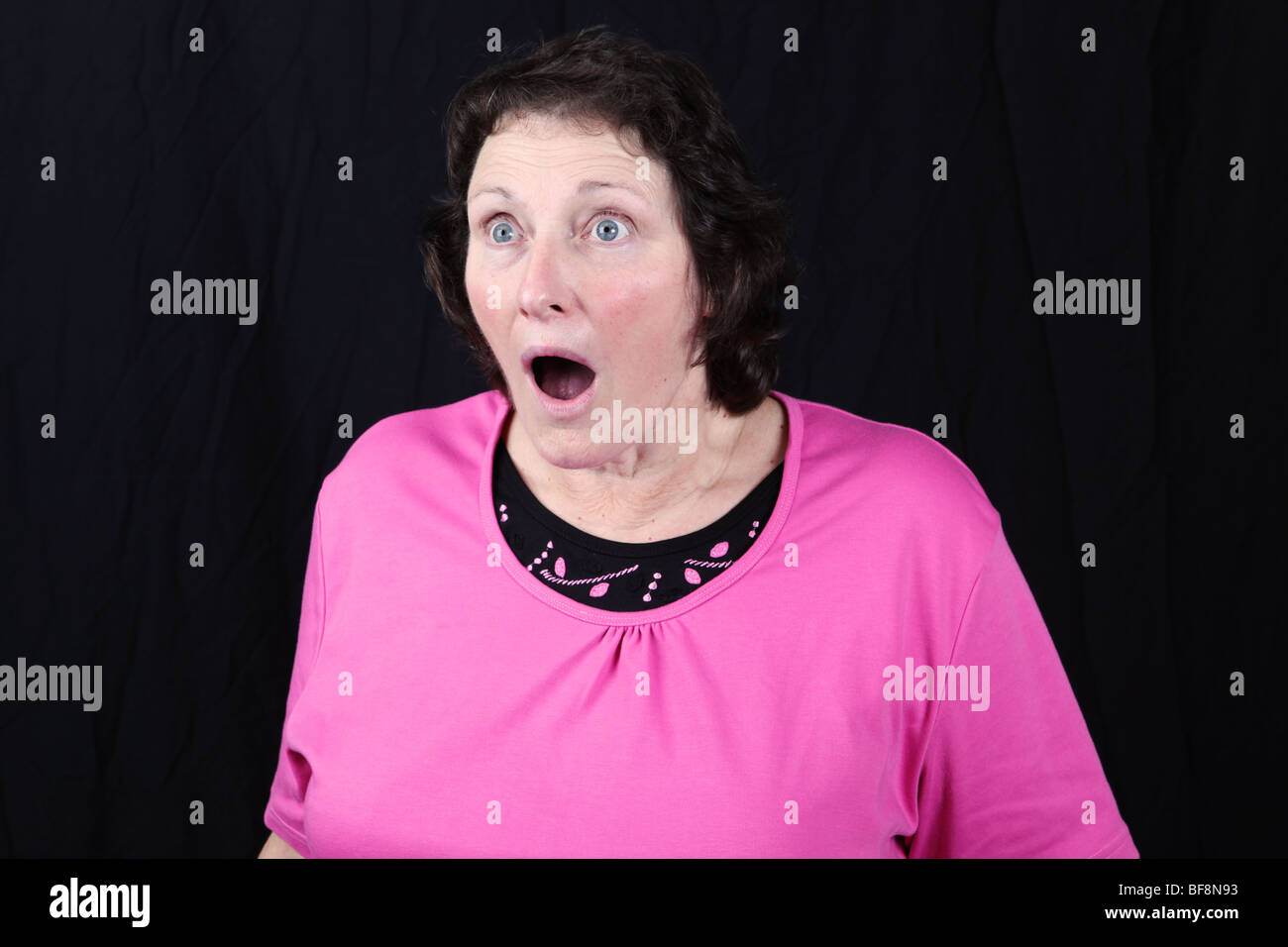 Late middle aged woman looking aghast surprised disbelieving shocked startled stunned hearing bad news - Stock Image