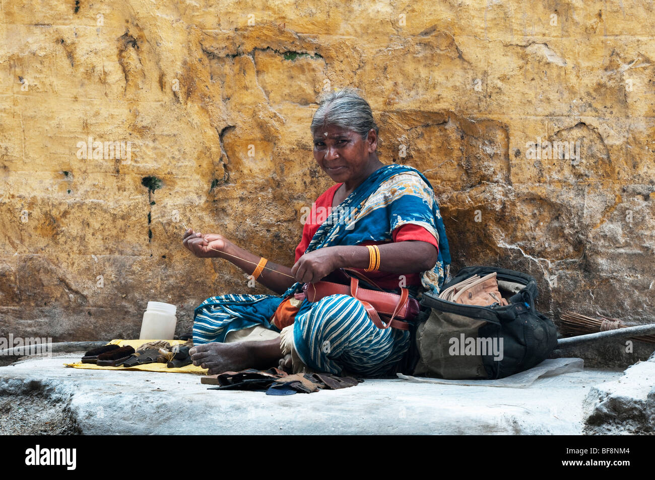 Old indian woman repairing leather goods sat on the street that is covered in bleaching powder in Puttaparthi, Andhra - Stock Image