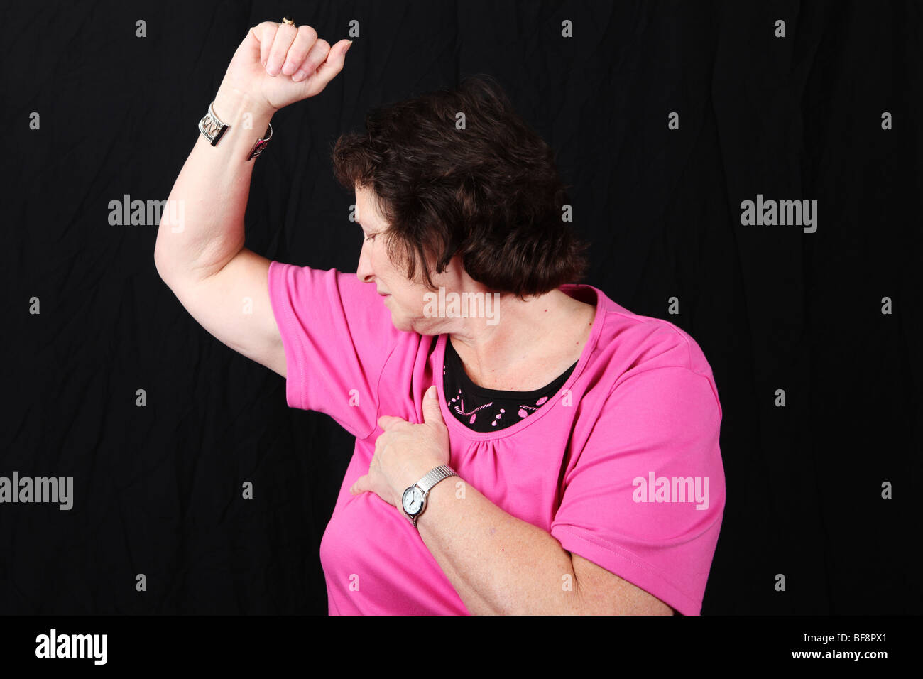 Late middle aged woman 50s 60s smelling own armpit with strong body odor odour poor personal hygiene unpleasant - Stock Image