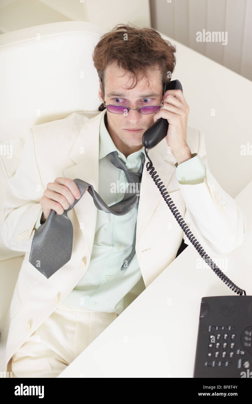 The young businessman speaks on the phone, worries and rumples a tie - Stock Image