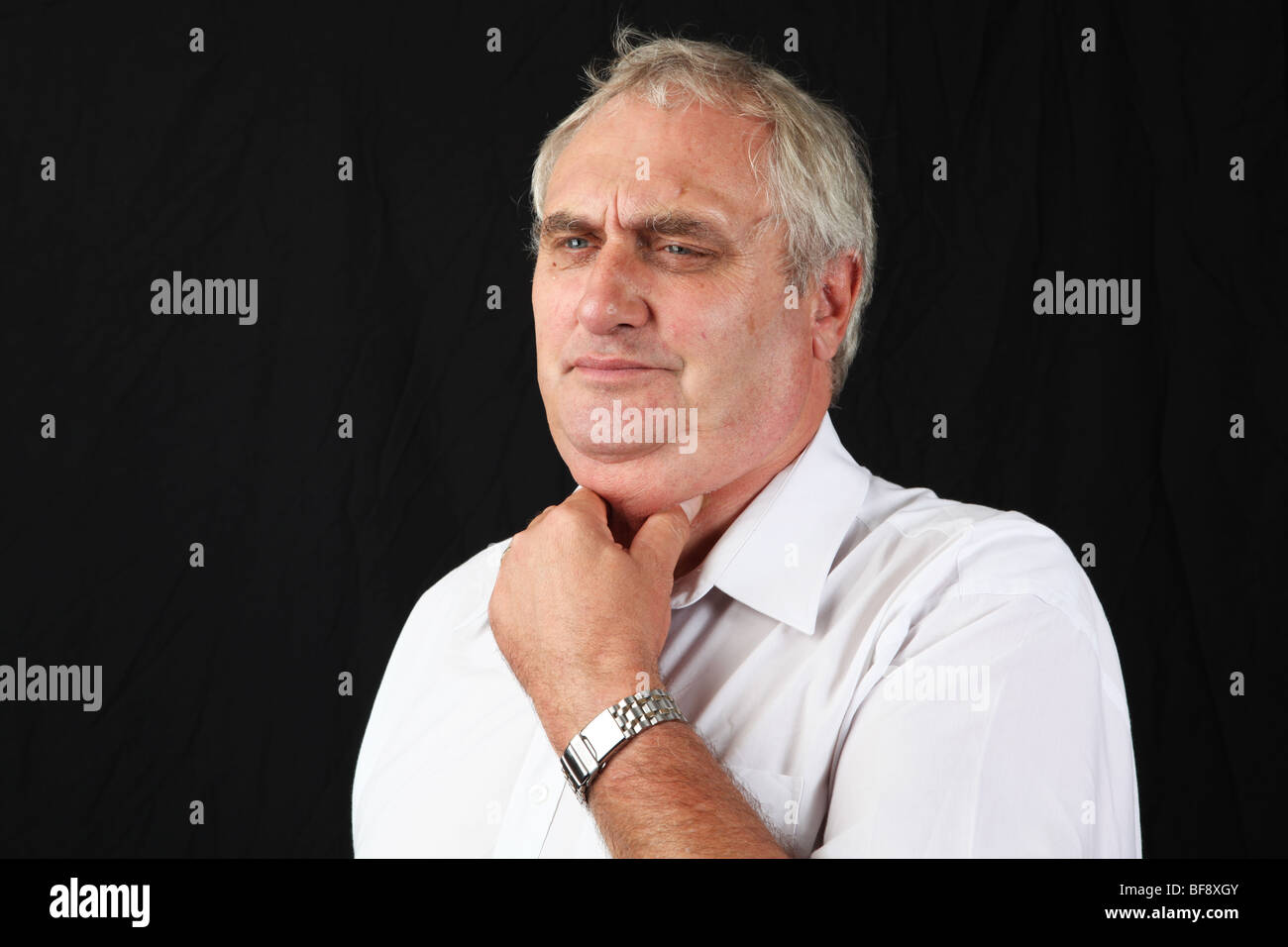 Mature late middle aged 50s 60s man holding neck suffering with sore throat common cold flu sick ill - Stock Image
