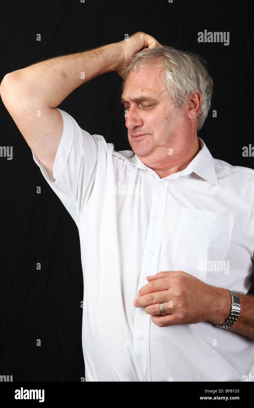 Late middle aged man sniffing smelling armpit checking for stale sweat sour underarm body odour odor poor personal - Stock Image