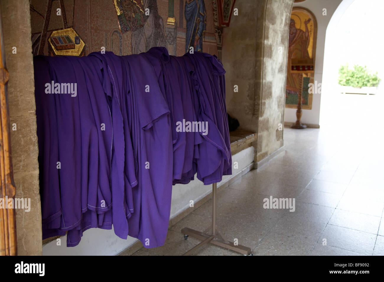 purple robes for visitors to cover up at the entrance of the Holy Royal and Stavropegiac Monastery of the Virgin - Stock Image