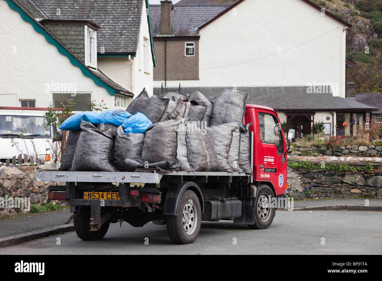 Britain, UK, Europe. Coal merchant delivering to a house with sacks of fuel on the truck - Stock Image