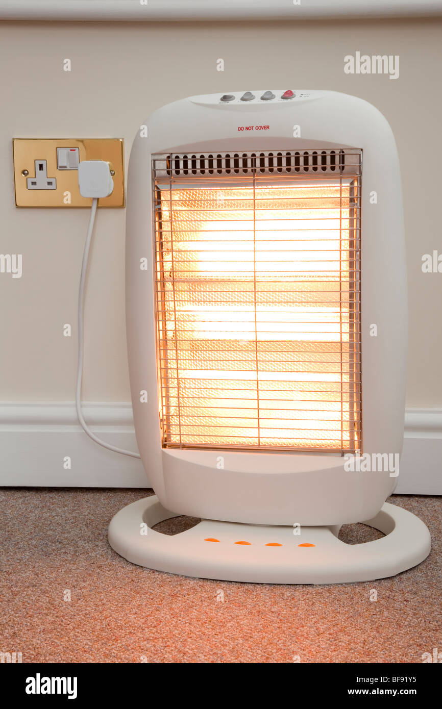 Electric halogen room heater with three heat settings plugged into electrical wall socket and switched on with high - Stock Image